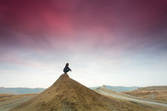 Silhouette of woman meditating on top of a hill. Stock Images