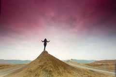 Silhouette of woman meditating on top of a hill. Stock Image