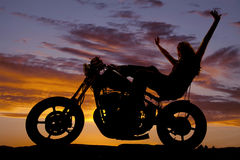 Silhouette woman on a motorcycle arms in air Royalty Free Stock Images
