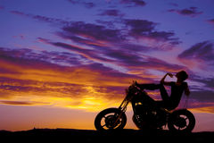 Silhouette woman on motorcycle finger on chin Stock Photography