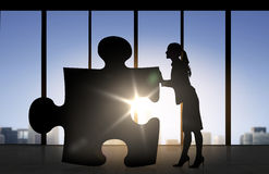 Silhouette of woman mowing puzzle over office Stock Image