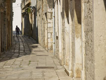 Silhouette of a woman. In a narrow street stock image