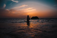 Silhouette of Woman On Ocean During Sunset Stock Photo