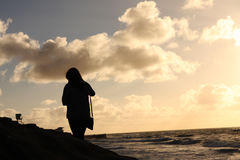 Silhouette of Woman by Ocean at Sunset Stock Photos