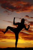 Silhouette of woman on one foot fists Stock Image