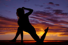 Silhouette of woman on one foot and one knee hand down Stock Photo