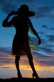 Silhouette of woman one hand on hat one on skirt Royalty Free Stock Photography