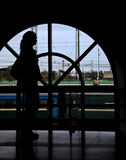 Silhouette woman opposite window railway station Stock Image