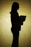Silhouette of woman with papers Stock Image
