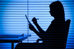 Silhouette of woman with papers (view through the blind) Stock Photos