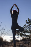 Silhouette of a woman performing Yoga with the sun shining behind her Royalty Free Stock Images