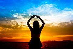 Silhouette of woman performs as yoga. Exercise on the beach during sunset Royalty Free Stock Image
