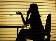 Silhouette of woman on the phone. (view through the blind Stock Photography