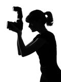 Silhouette woman photographer. Portrait silhouette in shadow of a young woman photographer holding a camera  in studio on white background isolated Royalty Free Stock Images