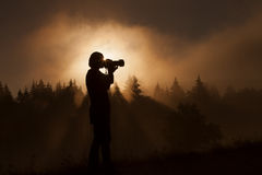 Silhouette of woman photographer taking photos in forest with fo Royalty Free Stock Photography