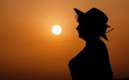 Silhouette woman portrait against orange sunset Stock Images