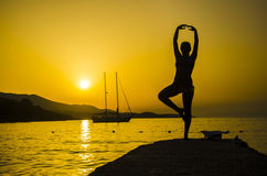 Silhouette of woman practicing yoga on the beach Royalty Free Stock Images