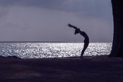 Silhouette of woman practicing yoga on the beach