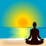 Silhouette of woman practicing yoga on the beach at sunrise Royalty Free Stock Photography