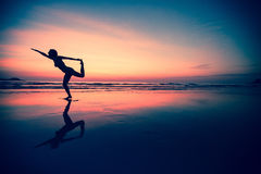 Silhouette of a woman practicing yoga. Stock Images