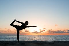 Silhouette of woman practicing yoga on the beach at sunset royalty free stock image