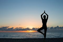 Silhouette of woman doing yoga on the beach at sunset stock image