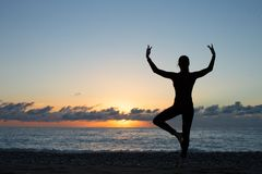 Silhouette of woman doing yoga on the beach at sunset royalty free stock photography