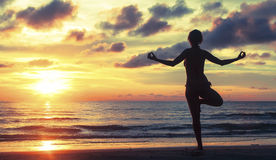 Silhouette of a woman practicing yoga during a beautiful sunset Stock Images