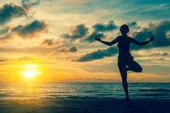 Silhouette woman practicing yoga on the coast Royalty Free Stock Photos