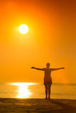 Silhouette of woman practicing yoga with raised arms on the sunset Stock Images