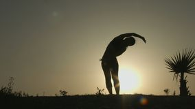 Silhouette of woman practicing yoga in rays of sunrise. Balance of body and mind stock footage