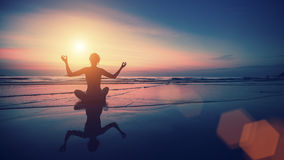 Silhouette of woman practicing yoga with the reflection on the wet sand. Stock Photography