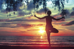Silhouette  woman practicing yoga on the sea beach at blood-surrealistic sunset. Royalty Free Stock Photo
