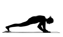 Silhouette of woman practising yoga exercises Stock Photography