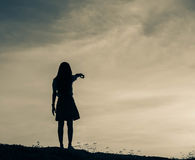 Silhouette of woman praying over beautiful sky background Royalty Free Stock Image