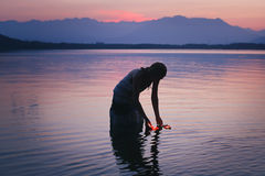 Silhouette of a woman in purple lake waters Stock Image