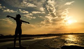 Silhouette of woman with raised hands on the beach. At sunset. Woman doing yoga, performing asanas and enjoying life on the sea. Vacation travel holidays and Royalty Free Stock Images