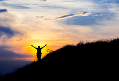 Silhouette of woman with raised hands Royalty Free Stock Photo