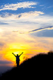 Silhouette of woman with raised hands Stock Image
