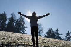 Female person breathing warm air during cold day. Silhouette of a woman raises her hands and breathing warm air during a cold winter morning. Selective focus stock photo