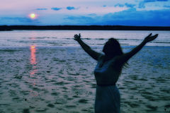 Silhouette of a Woman Raising Hands at Ocean. Silhouette of a woman raising her hands in worship at sunset at the ocean Royalty Free Stock Image