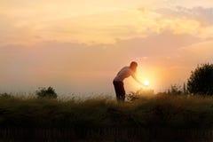 Silhouette of woman reaching hand to the sun beautiful field Stock Photo