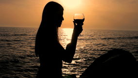 Silhouette of woman with red glass of wine during sunset on the ocean Royalty Free Stock Photo