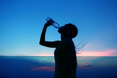 Silhouette of woman Rehydrate and refresh at sunset Royalty Free Stock Image