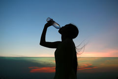 Silhouette of woman Rehydrate and refresh at sunset Stock Image
