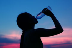 Silhouette of woman Rehydrate and refresh at sunset Stock Photo