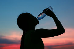 Silhouette of woman Rehydrate and refresh at sunset Stock Photography