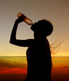 Silhouette of woman Rehydrate and refresh at sunset Royalty Free Stock Photo