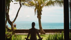 Silhouette of woman is relaxing by practicing yoga in lotus position from bungalow on the ocean beach of Bali with beautiful view