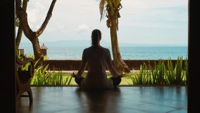 Silhouette of woman relaxing by practicing yoga in lotus position from bungalow on the ocean beach, beautiful view, nature sounds. Silhouette of woman is stock video
